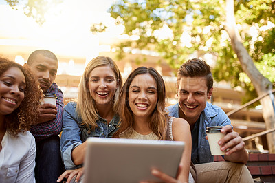 Buy stock photo Cropped shot of a group of young students using a digital tablet while enjoying their free time on campus