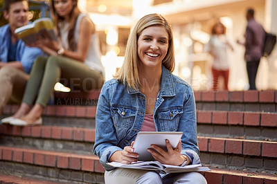 Buy stock photo Cropped portrait of an attractive young  female student using a digital tablet to study while sitting outdoors on campus