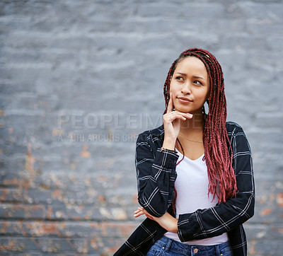Buy stock photo Cropped shot of an attractive young woman looking contemplative while standing against a grey wall
