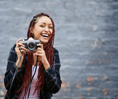 Buy stock photo Cropped shot of an attractive young woman using a camera to take a photograph while standing against a grey wall