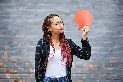 Buy stock photo Cropped shot of an attractive young woman looking skeptical while holding a speech bubble against a grey wall