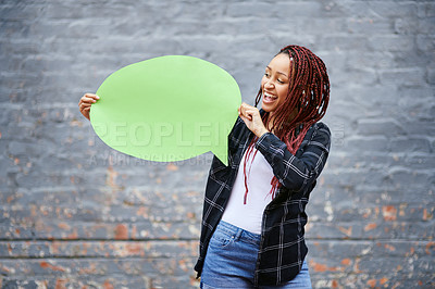 Buy stock photo Cropped shot of an attractive young woman holding a speech bubble while standing against a grey wall