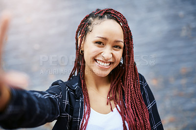Buy stock photo Cropped portrait of an attractive young woman taking a selfie while standing against a grey wall