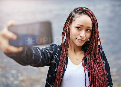 Buy stock photo Cropped shot of an attractive young woman taking a selfie with her smartphone while standing against a grey wall