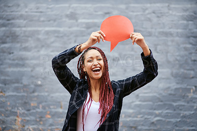 Buy stock photo Cropped portrait of an attractive young woman holding up a speech bubble while standing against a grey wall