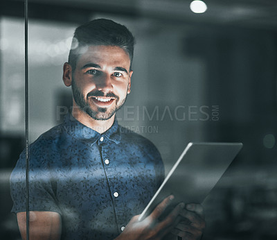 Buy stock photo Cropped portrait of a handsome young businessman working on his digital tablet late in the office