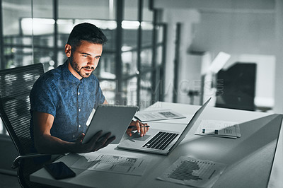 Buy stock photo Cropped shot of a handsome young businessman working late at night at his desk in the office