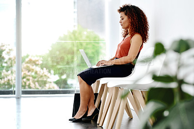 Buy stock photo Full length shot of an attractive young businesswoman using a laptop while sitting down and waiting for her interview
