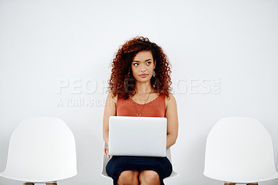 Buy stock photo Shot of an attractive young businesswoman using a laptop while sitting down and preparing for her interview