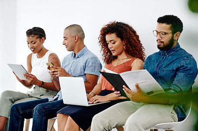 Buy stock photo Shot of a group of young businesspeople sitting down on chairs and preparing for their interviews