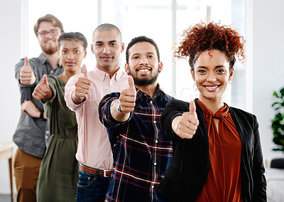 Buy stock photo Portrait of a group of young businesspeople posing with their thumbs up in an office