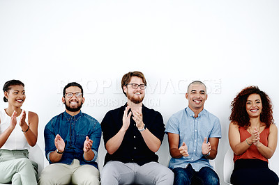 Buy stock photo Shot of young businesspeople sitting down and clapping while waiting for their interviews against a white background