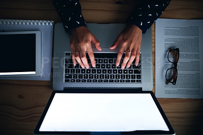 Buy stock photo High angle shot of an unrecognizable woman using her laptop while working late at the office
