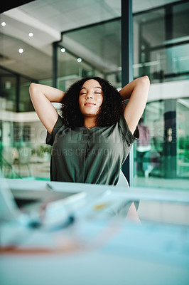 Buy stock photo Shot of a young businesswoman looking relaxed while sitting at her desk