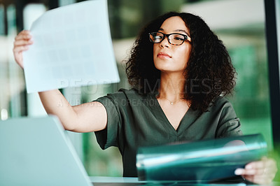 Buy stock photo Shot of a businesswoman looking at paperwork while sitting at her desk