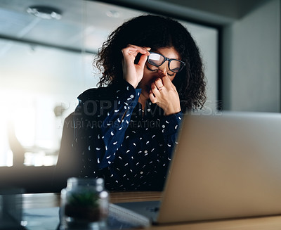 Buy stock photo Shot of a businesswoman rubbing her eyes while working late at the office