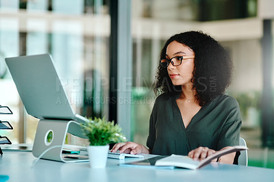 Buy stock photo Shot of a young businesswoman using her laptop at her desk