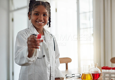 Buy stock photo Shot of an adorable little girl wearing a lab coat while conducting a scientific experiment