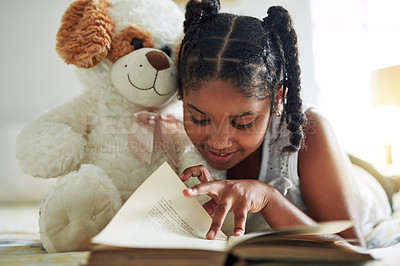 Buy stock photo Shot of a young girl lying on bed with her teddybear while reading a book