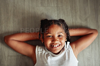 Buy stock photo Cropped shot of an adorable little girl lying on the floor