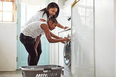 Buy stock photo Shot of a mother and daughter doing washing at home