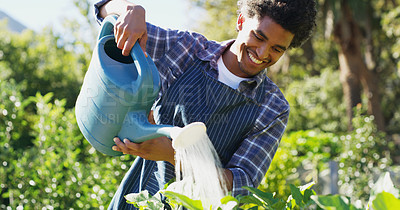 Buy stock photo Cropped shot of a handsome young male farmer watering his crops on the farm