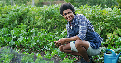 Buy stock photo Portrait of a handsome young male farmer using a tablet while checking on his crops on the farm