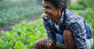 Buy stock photo Cropped shot of a handsome young male farmer checking this soil on his farm