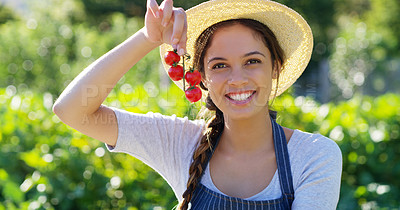 Buy stock photo Cropped portrait of an attractive young female farmer holding a bunch of strawberries while standing on her farm