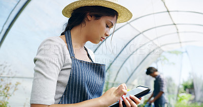 Buy stock photo Cropped shot of an attractive young female farmer using a tablet while working in a greenhouse on the farm with hers husband in the background