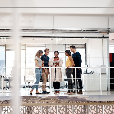 Buy stock photo Full length shot of a diverse group of colleagues at work discussing ideas on a tablet in the office