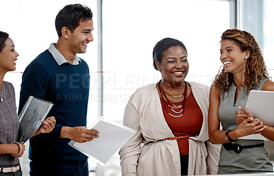 Buy stock photo Cropped shot of a young diverse group of colleagues sharing a laugh together in the office