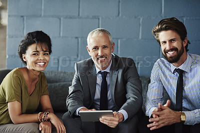 Buy stock photo Cropped portrait of three businesspeople working together on a digital tablet in their office