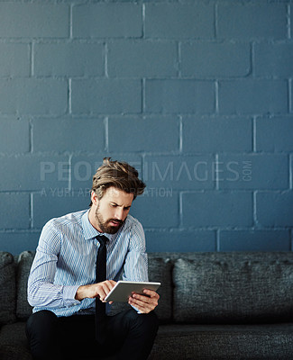 Buy stock photo Cropped shot of a handsome young businessman using his tablet while sitting on a sofa in the office