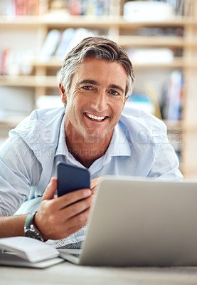 Buy stock photo Cropped portrait of a handsome mature man lying on his living room floor using a cellphone and laptop