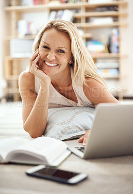 Buy stock photo Cropped portrait of a beautiful mature woman lying on her living room floor using a laptop