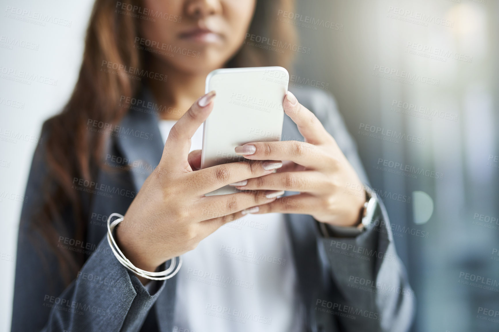 Buy stock photo Cropped shot of a young businesswoman using a smartphone in a modern office