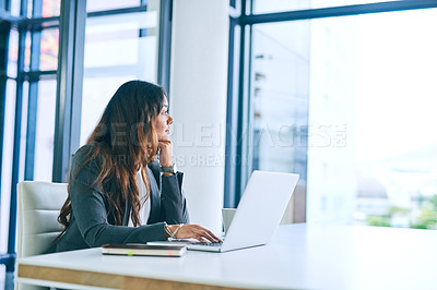 Buy stock photo Shot of a young businesswoman using a laptop and looking thoughtful in a modern office