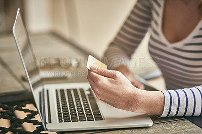 Buy stock photo Cropped shot of an unrecognizable young woman using her laptop and credit card to shop online