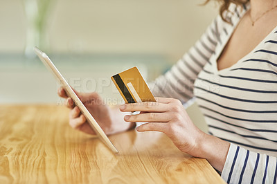 Buy stock photo Cropped shot of an unrecognizable young woman using her digital tablet and credit card to shop online