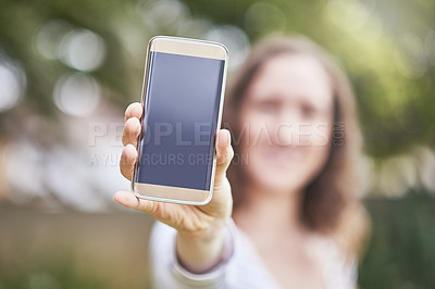 Buy stock photo Cropped portrait of an unrecognizable young woman holding up a mobile phone while standing outdoors