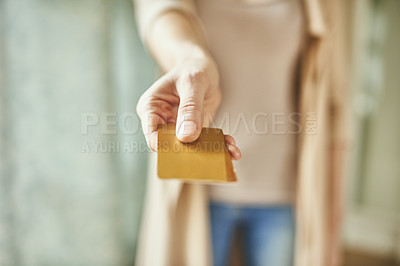 Buy stock photo Cropped shot of an unrecognizable young woman holding out her credit card indoors
