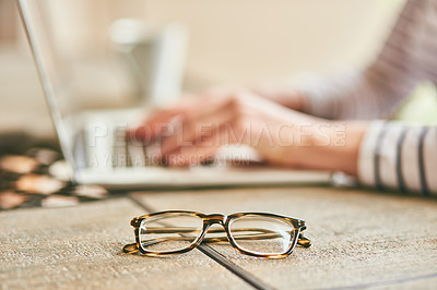 Buy stock photo Cropped shot of an unrecognizable young woman's spectacles placed on a desk at home