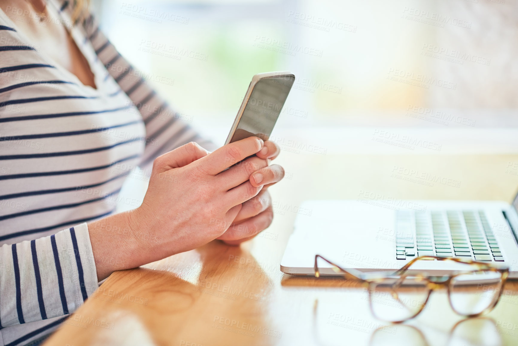 Buy stock photo Cropped shot of an unrecognizable young woman using her cellphone while working in her home office