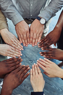 Buy stock photo High angle shot of a group of businesspeople joining their hands together in a solidarity
