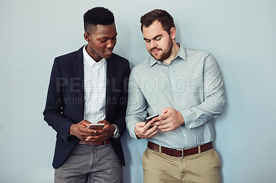 Buy stock photo Studio shot of two young businessmen using their smartphones against a grey background