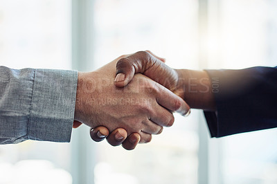 Buy stock photo Cropped shot of two businessmen shaking hands in a modern office