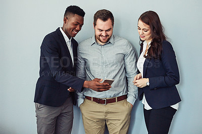 Buy stock photo Studio shot of a group of young businesspeople using a smartphone together against a grey background