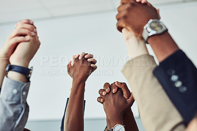 Buy stock photo Cropped shot of a group of businesspeople holding hands in solidarity