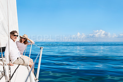 Buy stock photo Full length portrait of an affectionate mature couple enjoying a boat cruise out on the ocean